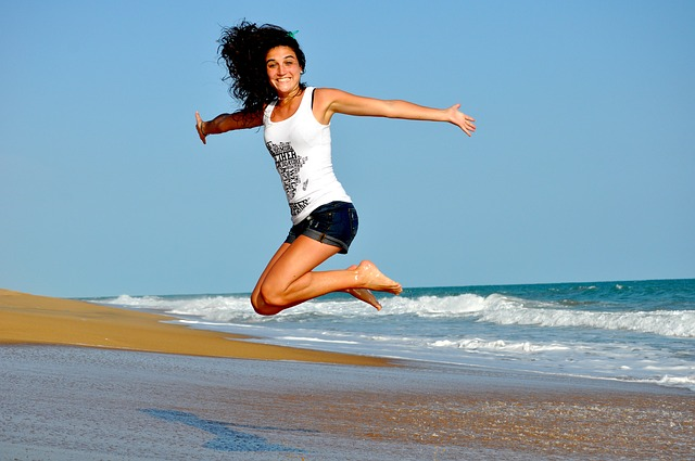 Image of In-Good-Place-Grants-Open Happy jumping woman on beach